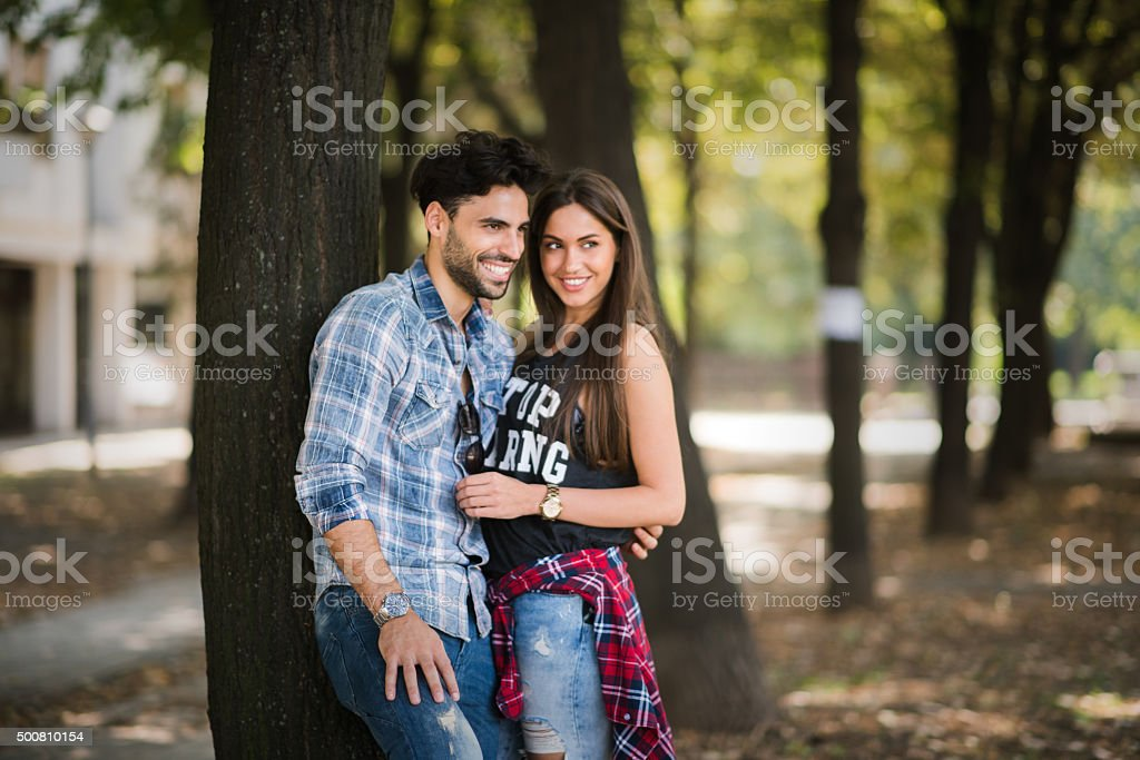 Young happy couple standing next to a tree stock photo