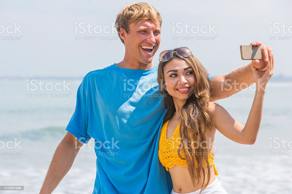 Young Happy Couple Taking Selfie Self Portraits at the Beach stock photo