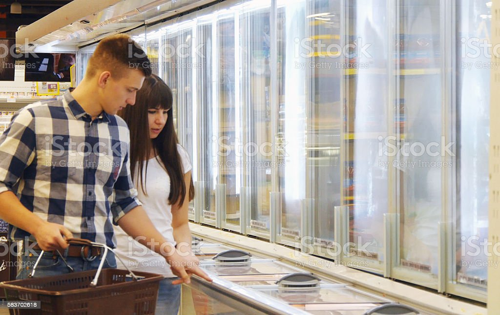 Young happy couple walking in store, stopping near the freezer foto de stock libre de derechos