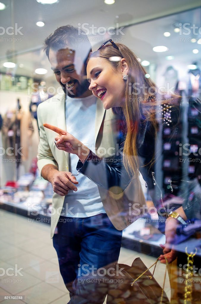 young  happy couple window shopping at a mall stock photo