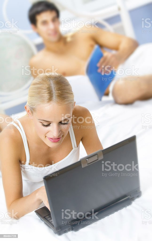 Young happy couple with laptop in bedroom. Focus on woman. royalty-free stock photo