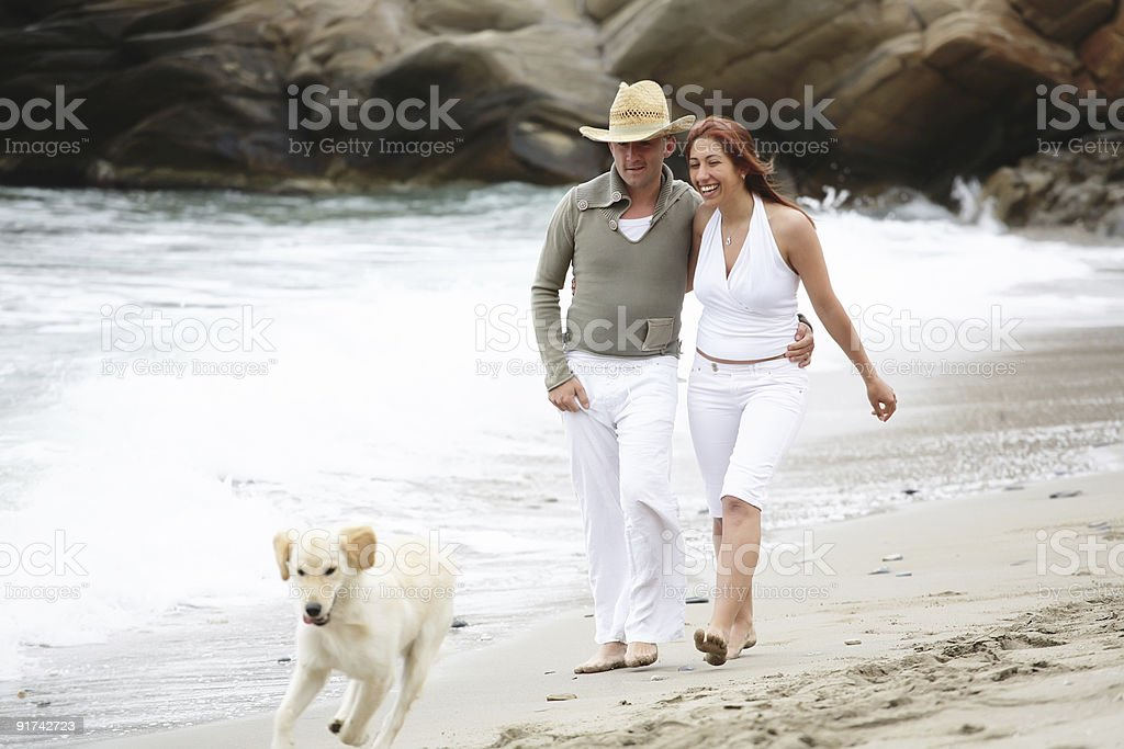 Young happy couple with their dog on the beach royalty-free stock photo