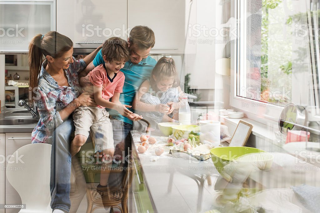 Young happy family having fun together in the kitchen. stock photo