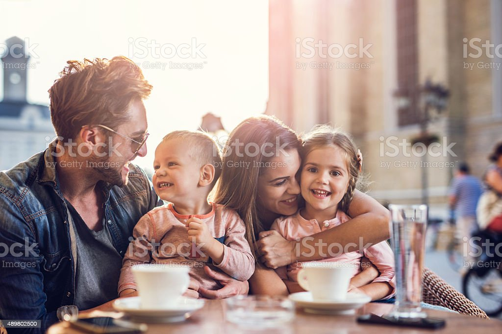 Young happy family spending a day in a city cafe. stock photo