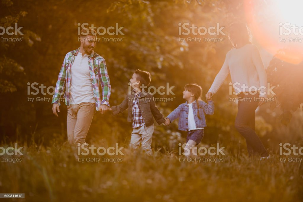 Smiling family enjoying a day together while holding hands and...