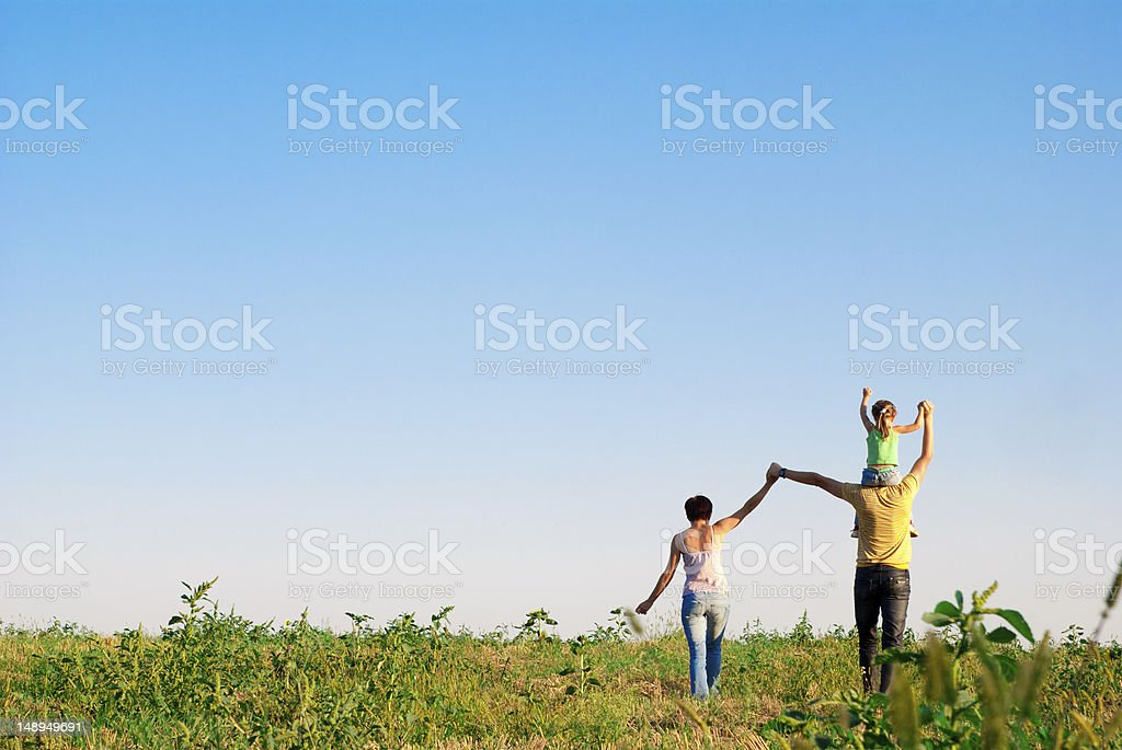 Young happy family walking away in a field stock photo