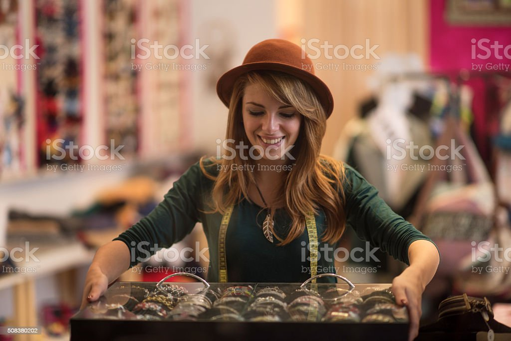 Young happy fashion designer working in her store. stock photo