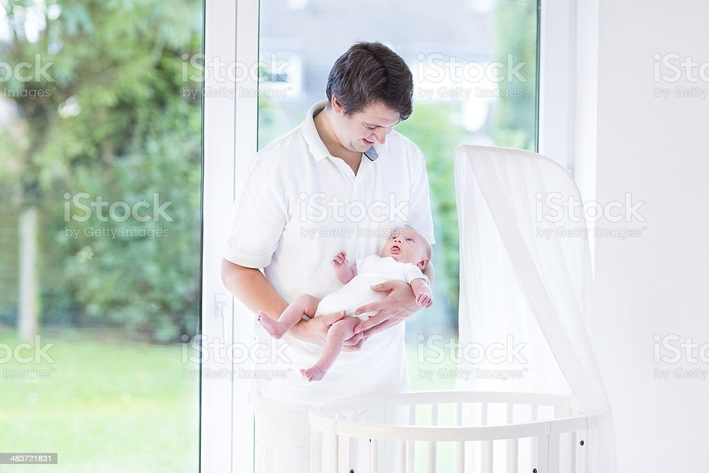 Young happy father and newborn baby near white round crib royalty-free stock photo