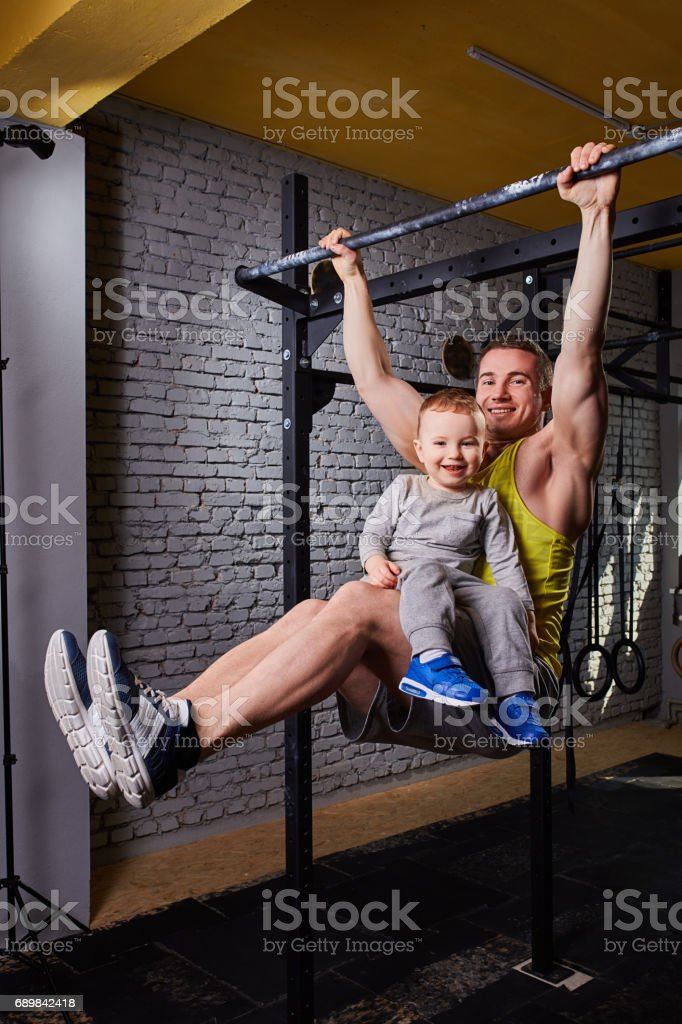 Young happy father doing pull ups on the bar with son on his legs at the gym against brick wall. stock photo