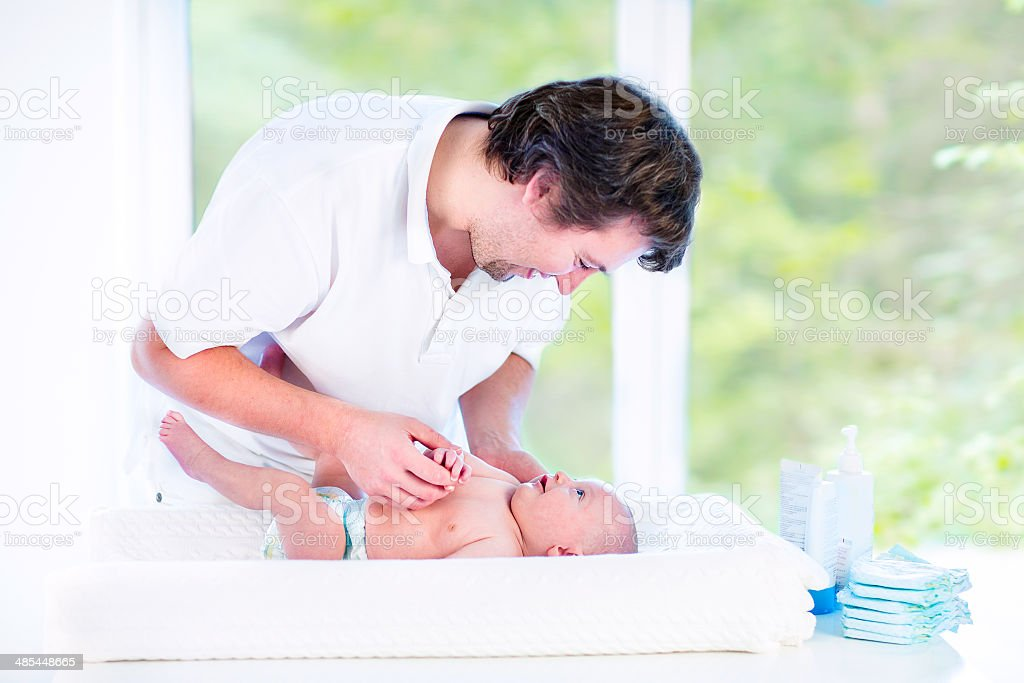 Young happy father playing with newborn son while changing diaper royalty-free stock photo