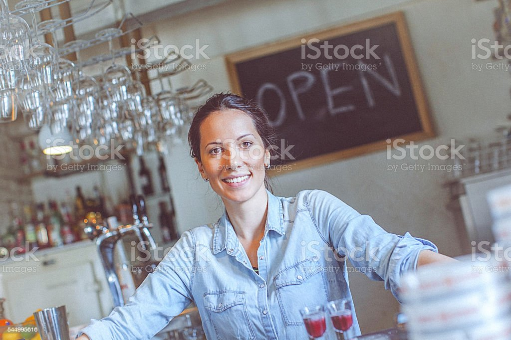 Young happy female bar owner posing at the bar counter stock photo