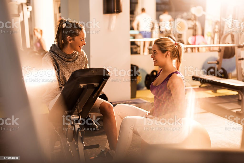 Young happy female friends talking to each other at gym. stock photo
