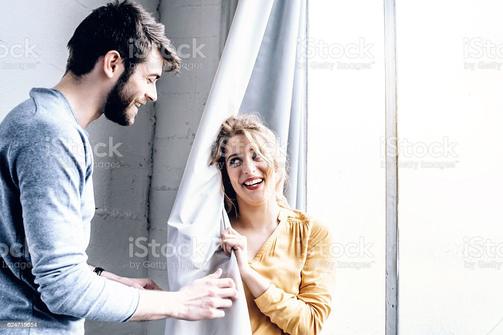 young happy french couple playing hide and seek with curtain stock photo