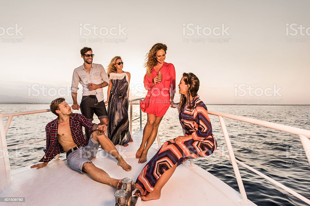 Young happy friends relaxing on a yacht and communicating. stock photo