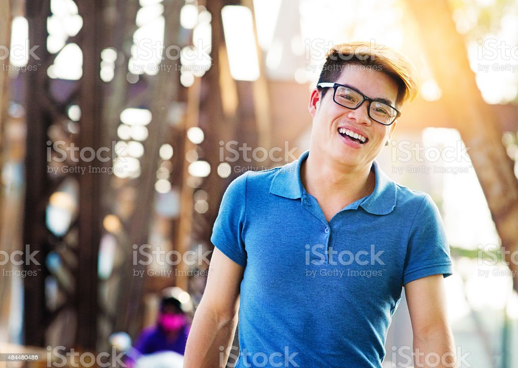 Young happy handsome Vietnamese man smiling Long Bien bridge Hanoi stock photo