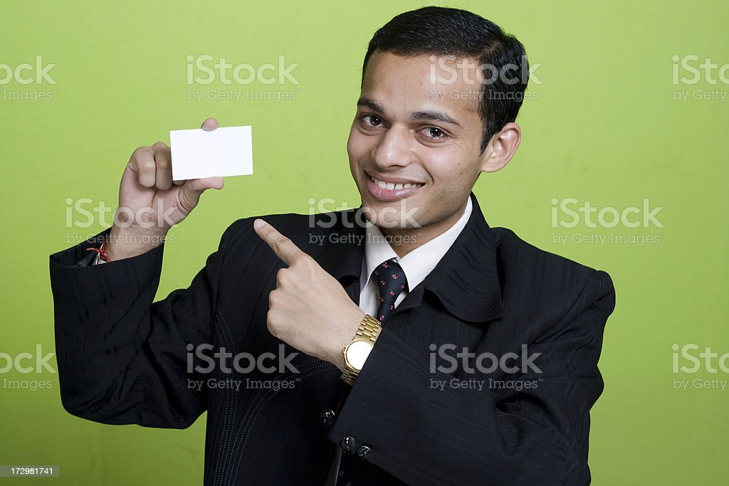 Young Happy Indian Businessman pointing finger at Blank business card royalty-free stock photo