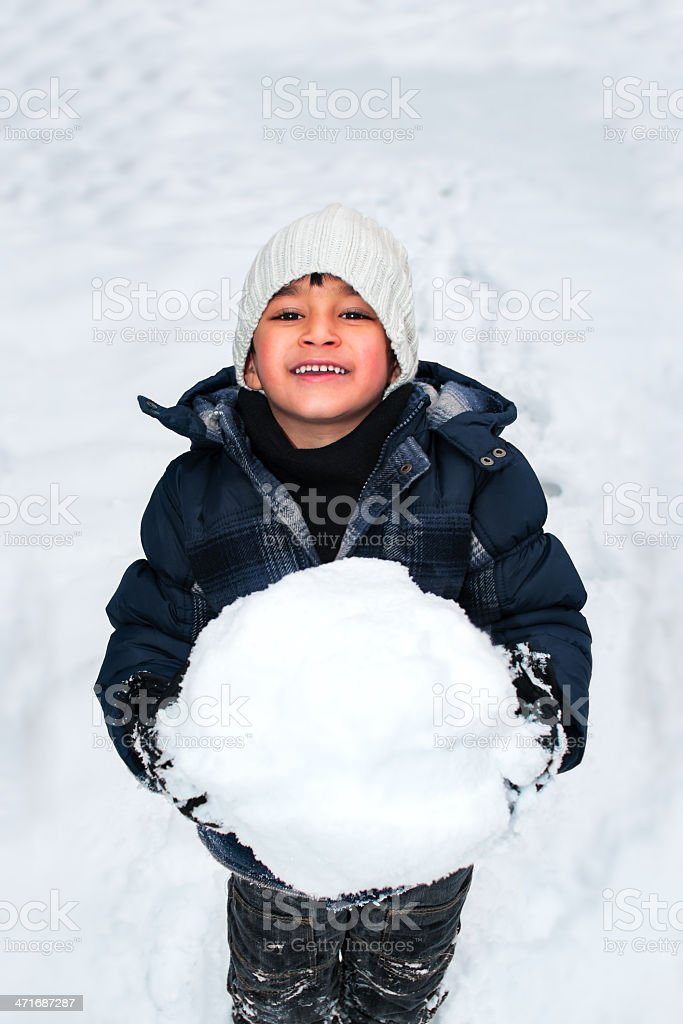Young happy kid child playing with a big snow ball royalty-free stock photo
