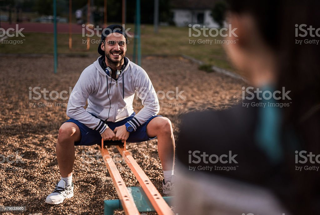 Young happy man having fun with his girlfriend on seesaw. stock photo