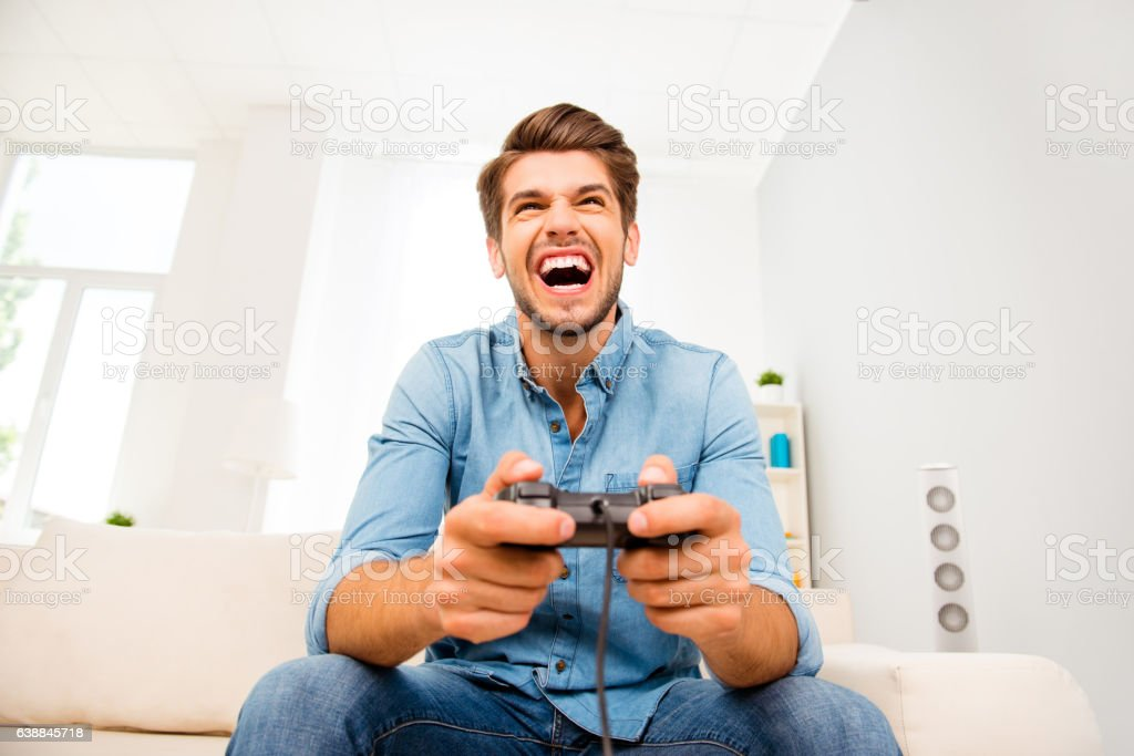 Young happy man laughing and playing video games on weekend stock photo