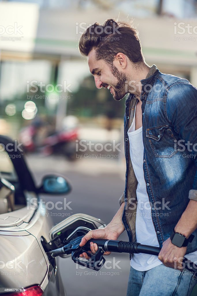 Young happy man pumping gas at gas station. stock photo