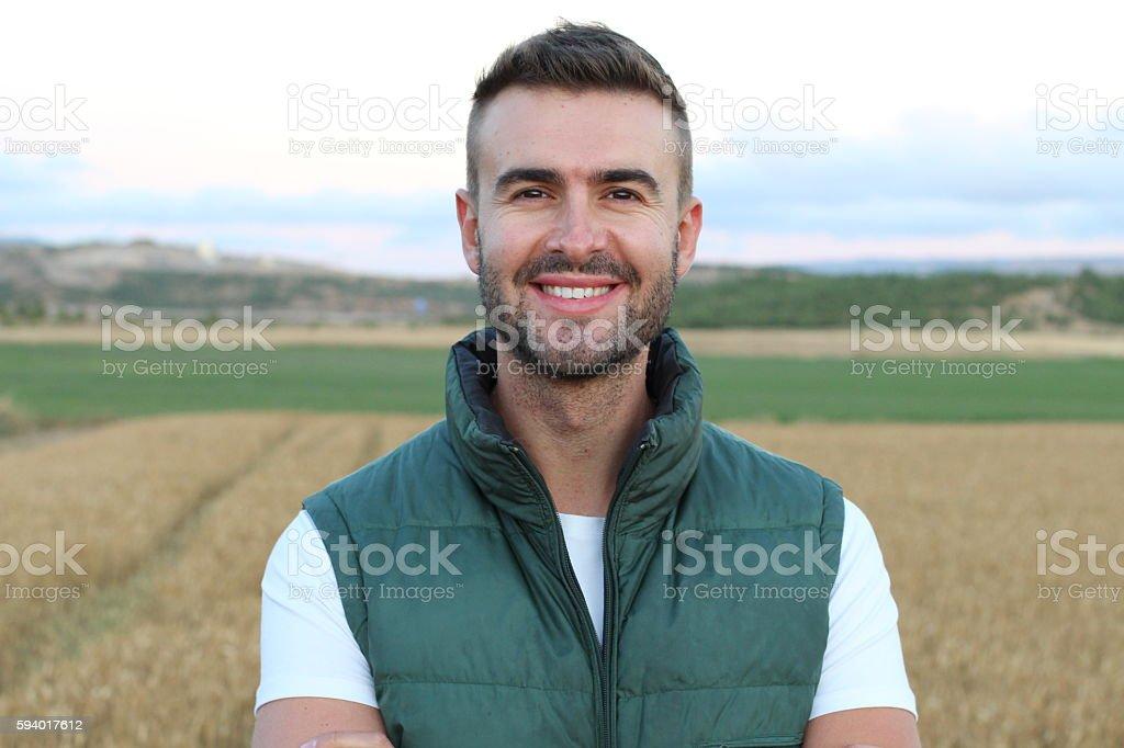 Young happy man smiling at camera outdoors stock photo