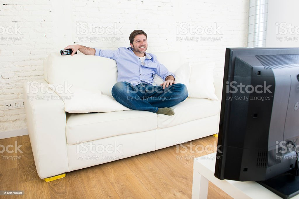young happy man watching television smiling and laughing in sofa stock photo