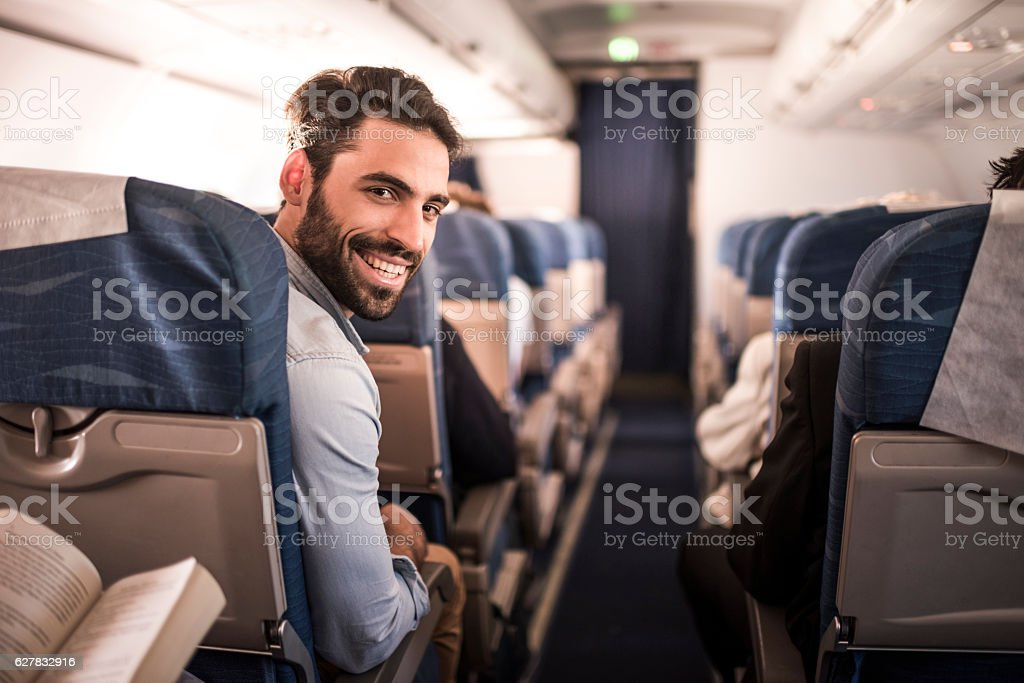 Young happy passenger flying in the airplane. stock photo