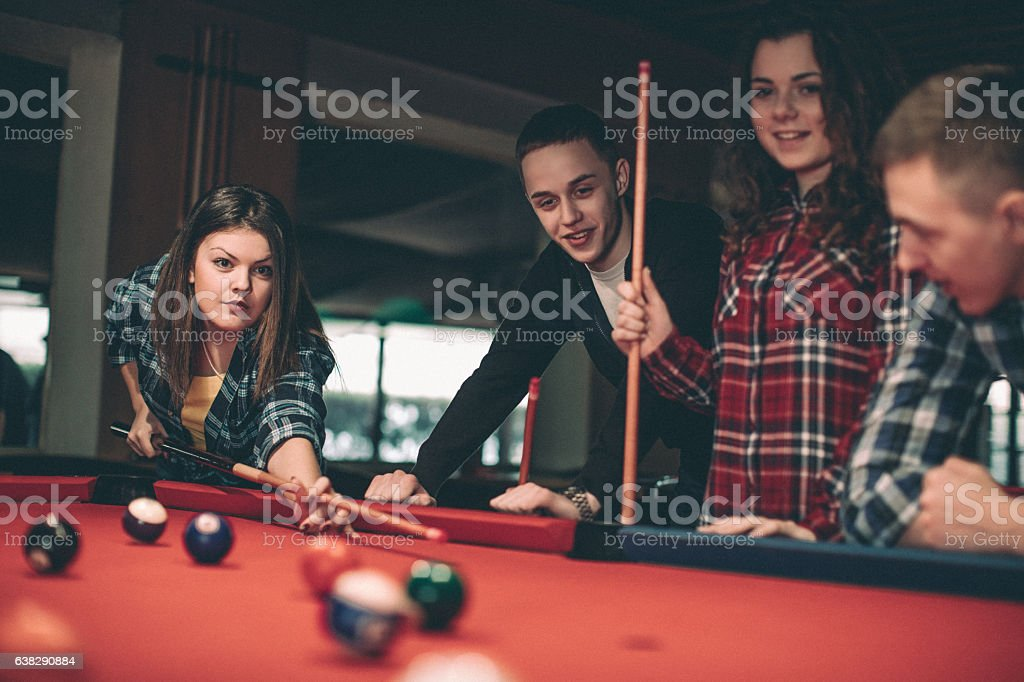 Young happy people communicating and playing billiard stock photo