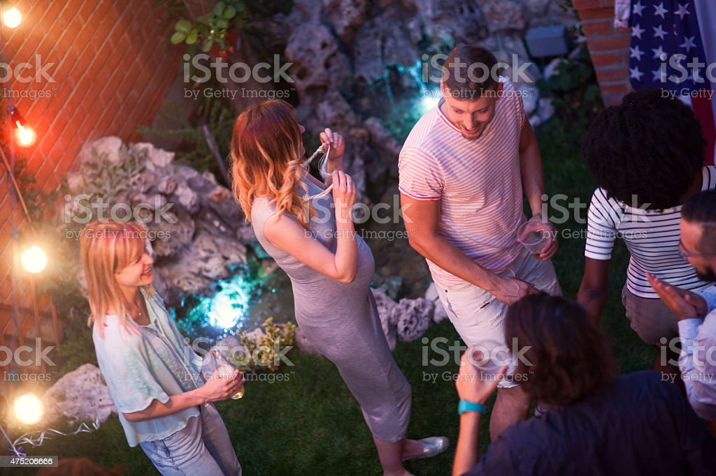 Young Happy People Dancing At Backyard Party. stock photo