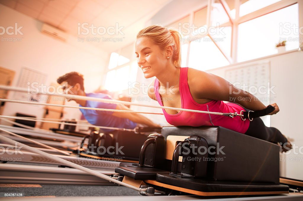 Young happy people exercising on Pilates machines at health club. stock photo