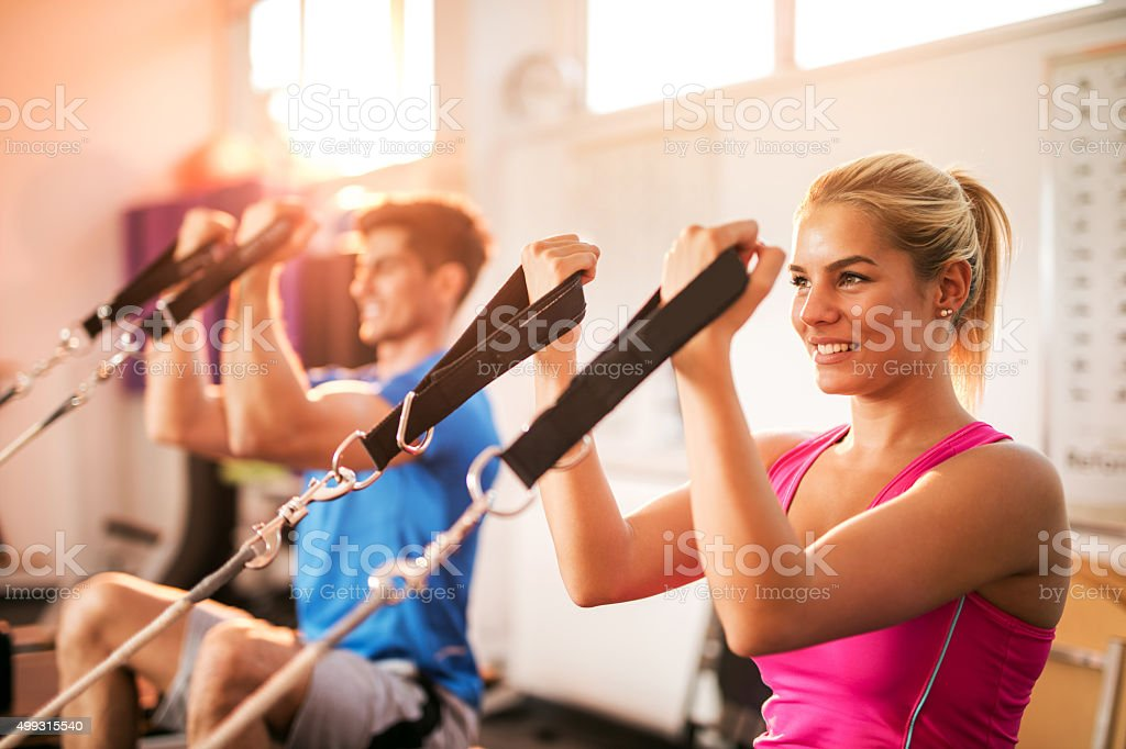 Young happy people exercising on Pilates training class. stock photo