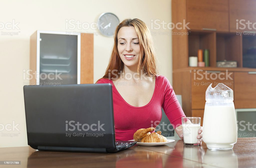Young happy red-haired girl in pink using laptop during breakfas royalty-free stock photo