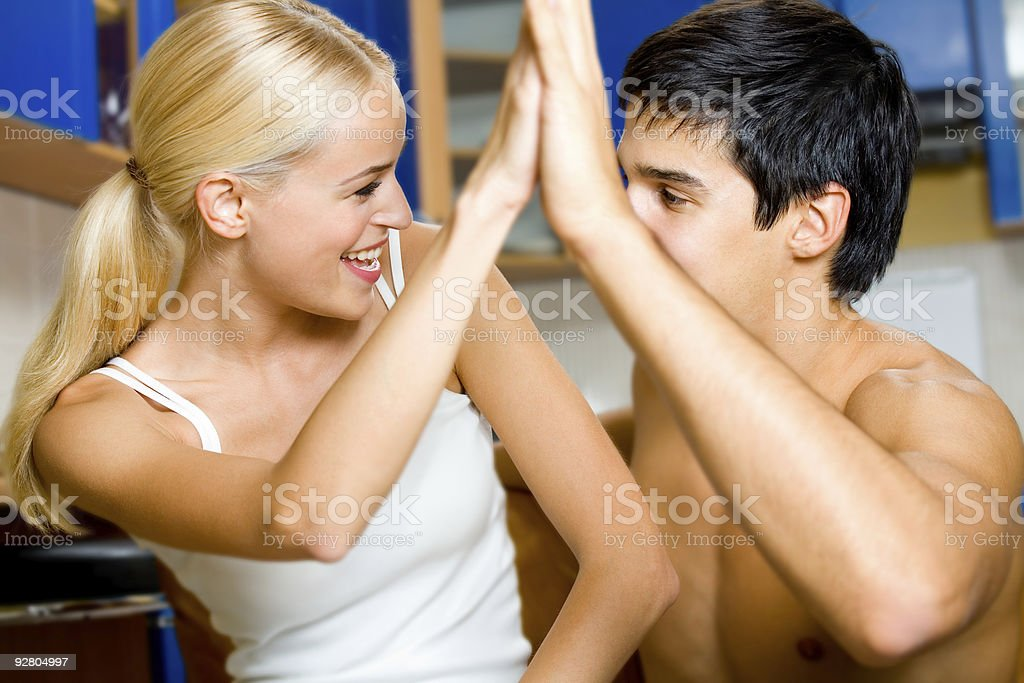 Young happy smiling amorous couple gesturing a victory, at home royalty-free stock photo