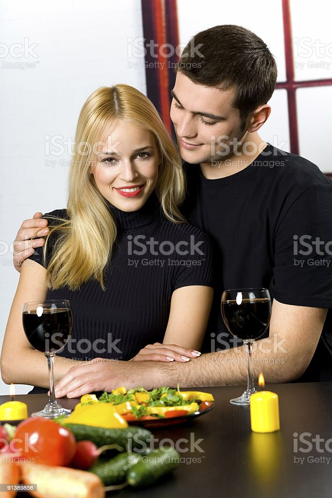 Young happy smiling couple celebrating with red wine at kitchen royalty-free stock photo