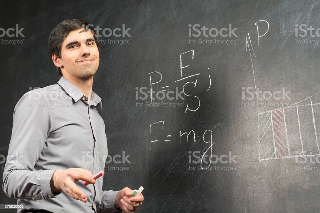 Young happy smiling teacher man standing near chalkboard stock photo