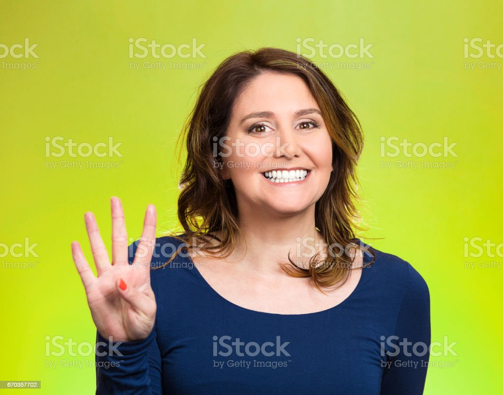 young, happy, smiling woman, making four, 4 times sign gesture with hand fingers stock photo