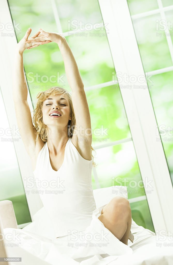 Young happy smiling woman waking up at bedroom royalty-free stock photo