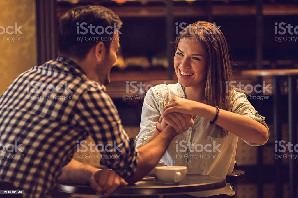 Young happy woman arm wrestling with her boyfriend. stock photo