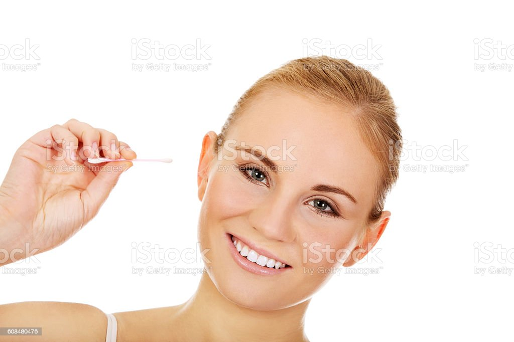 Young happy woman cleans her ear stock photo