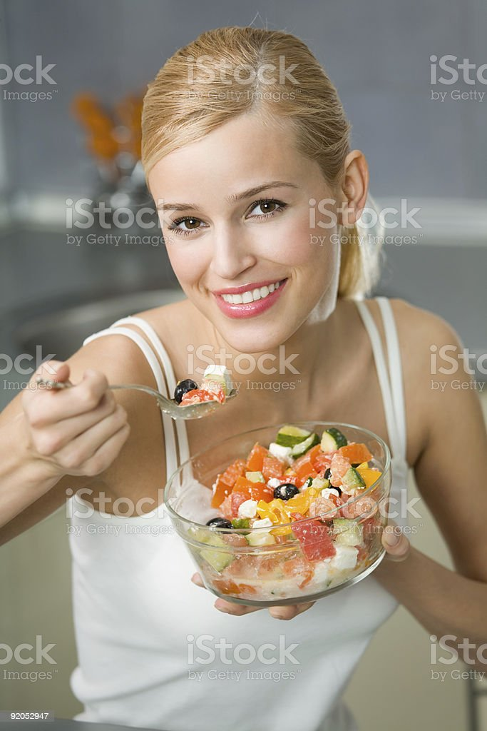 Young happy woman eating salad at domestic kitchen royalty-free stock photo