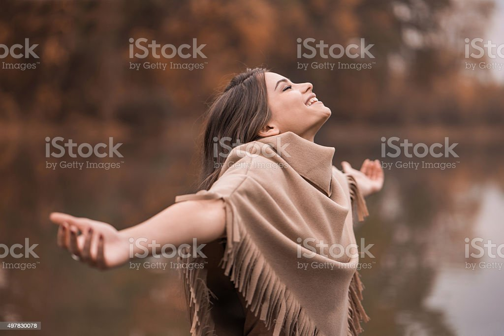 Young happy woman enjoying in autumn day near the river. stock photo