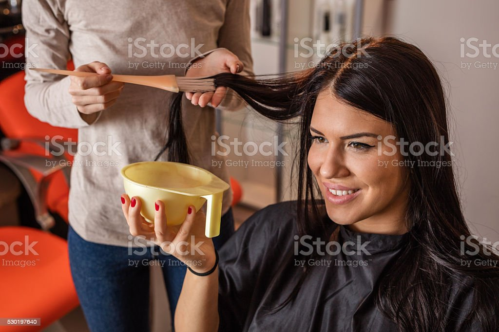 Young happy woman getting her hair dyed at home. stock photo