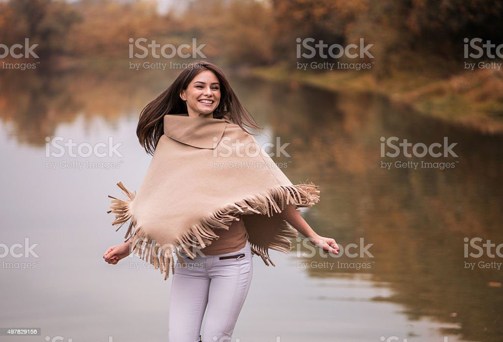 Young happy woman having fun near the river. stock photo