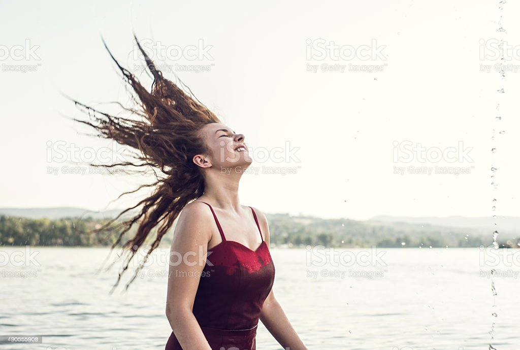 Young happy woman having fun with her hair in river. stock photo