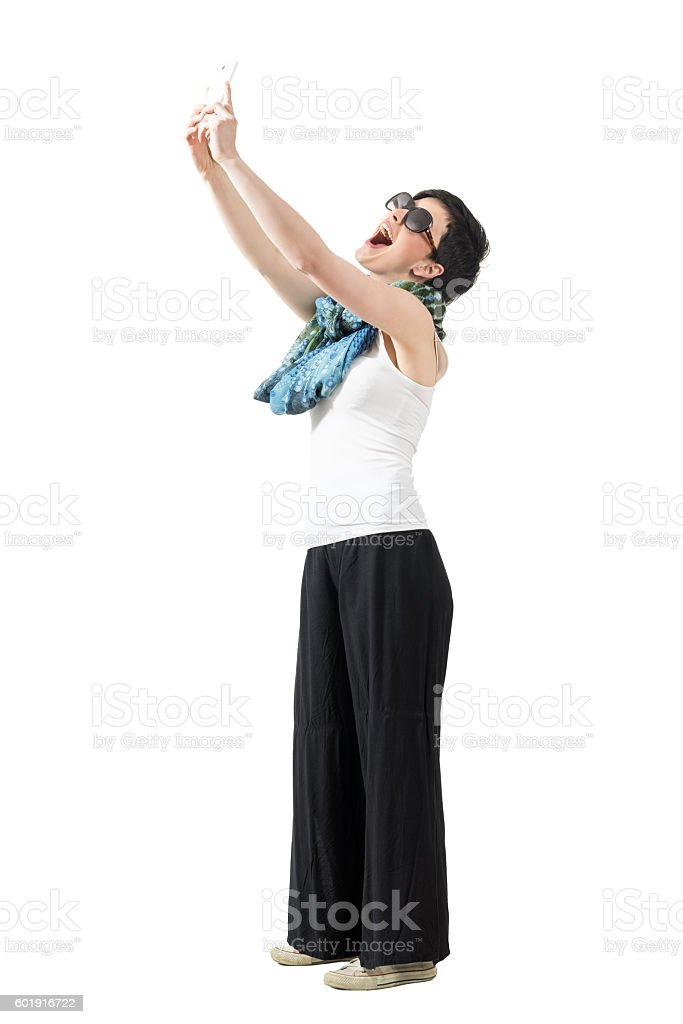 Young happy woman laughing and taking selfie from high angle stock photo
