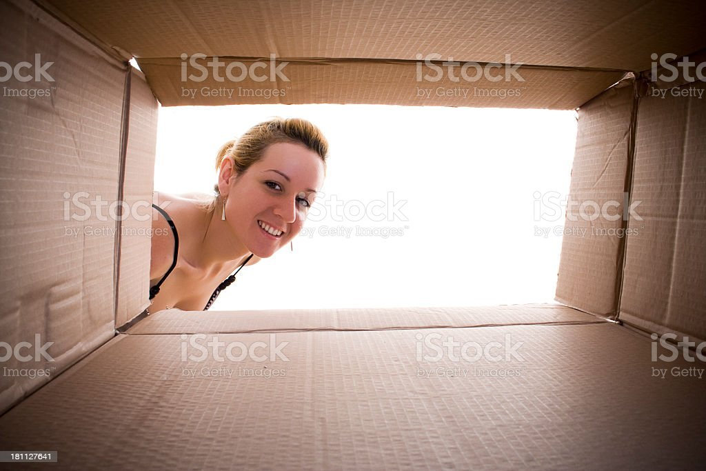 Young happy woman looking in to cardboard box. royalty-free stock photo