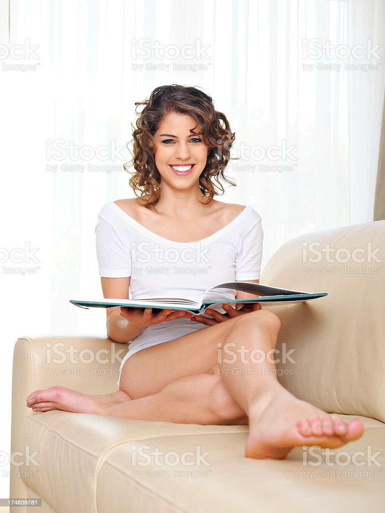 Young happy woman reading a book in the living room royalty-free stock photo