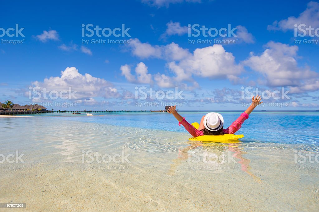 Young happy woman relaxing with air mattress during tropical vacation stock photo
