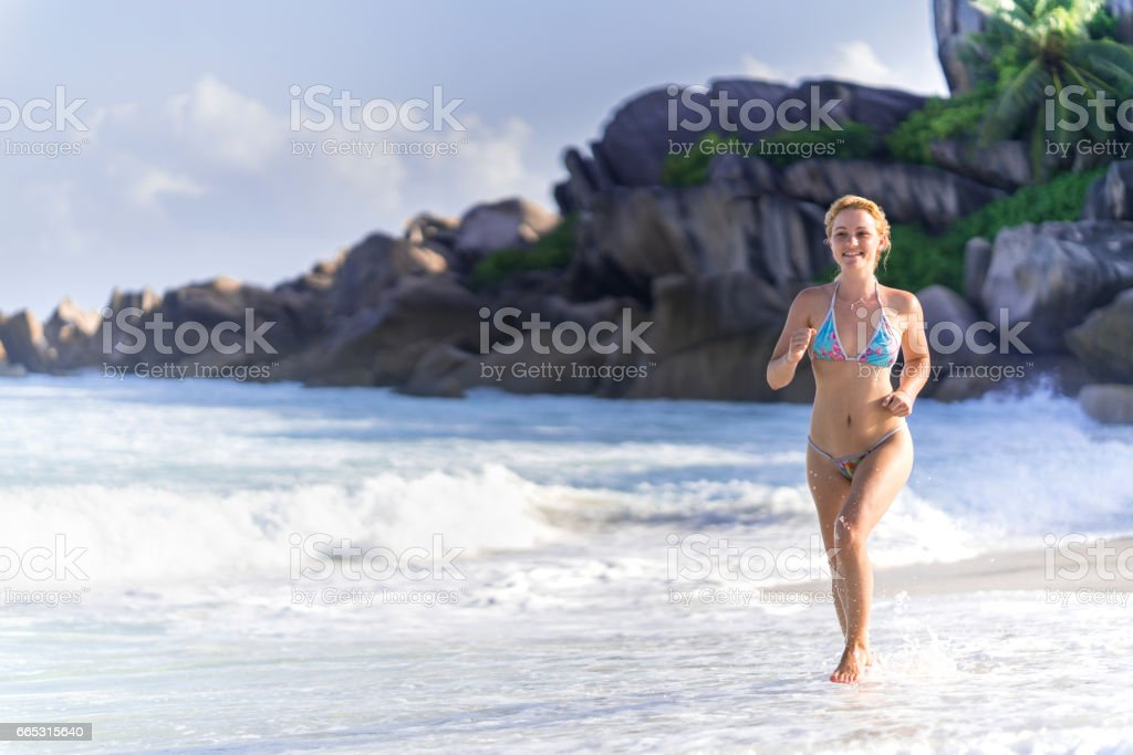 Young happy woman running on the beach during summer day. stock photo