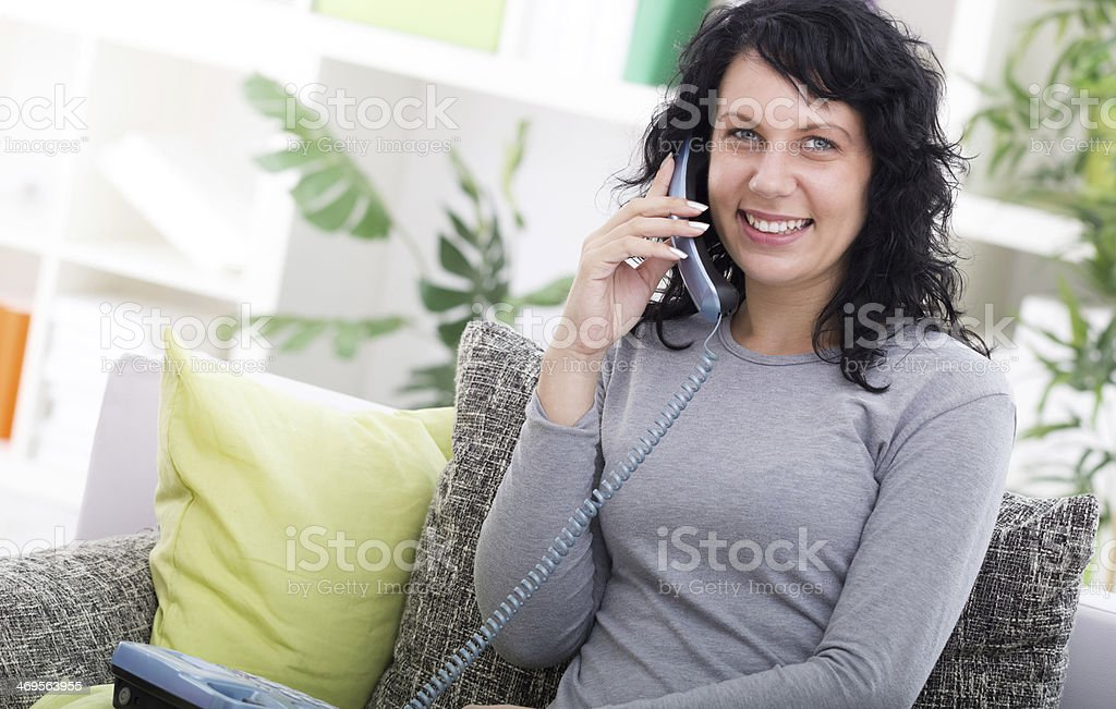 Young happy woman sitting on the sofa at home stock photo